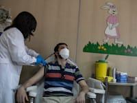 מתחסן באתונה, יוון. המדינה מציעה 150 יורו לכל צעיר שיגיע להתחסן / צילום: Associated Press, Petros Giannakouris