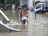 גבר נושא אישה בעיר הסינית ג'נגג'ואו לאחר שגשם חזק גרם להצפות באזור בשבוע שעבר / צילום: Reuters, CHINA DAILY