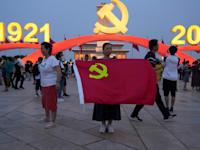 אישה מחזיקה בדל המפלגה הסינית בעת חגיגות מאה שנים להיווסדות המפלגה / צילום: Associated Press, Ng Han Guan