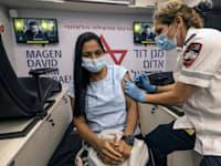 אישה מקבלת מנת חיסון שלישית בעמדת מד''א בתל אביב / צילום: Associated Press, Tsafrir Abayov