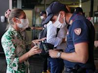 שוטר בתחנת רכבת במילאנו בודק תו ירוק של נוסעת, בתחילת ספטמבר / צילום: Associated Press, Luca Bruno