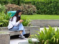 אישה צעירה בטלפון שלה בסינגפור / צילום: Shutterstock, ד''ר דייויד סינג