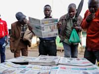 קנייאתים מעיינים בעיתונים המקומיים שדיווחו בהרחבה על חשבונות הבנק הסודיים של הנשייא, שנחשפו במסמכי פנדורה, השבוע / צילום: Associated Press, Brian Inganga