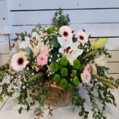 Cesto de mimbre con flores de temporada y eucaliptus