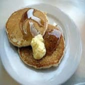 Two fluffy pancakes served with butter & Syrup