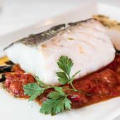 Lomo de bacalao con asadillo de pimientos y salsa de chipirón