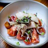 Tomates de temporada en ensalada con bonito y anchoas
