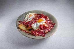 Huevos rotos con patatas fritas y jamón ibérico