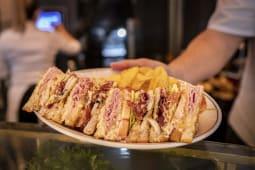 Sándwich club con pollo, bacón, lechuga, tomate y salsa especial