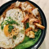Cazuela de arroz con huevo frito, salsa de cacahuete y sésamo