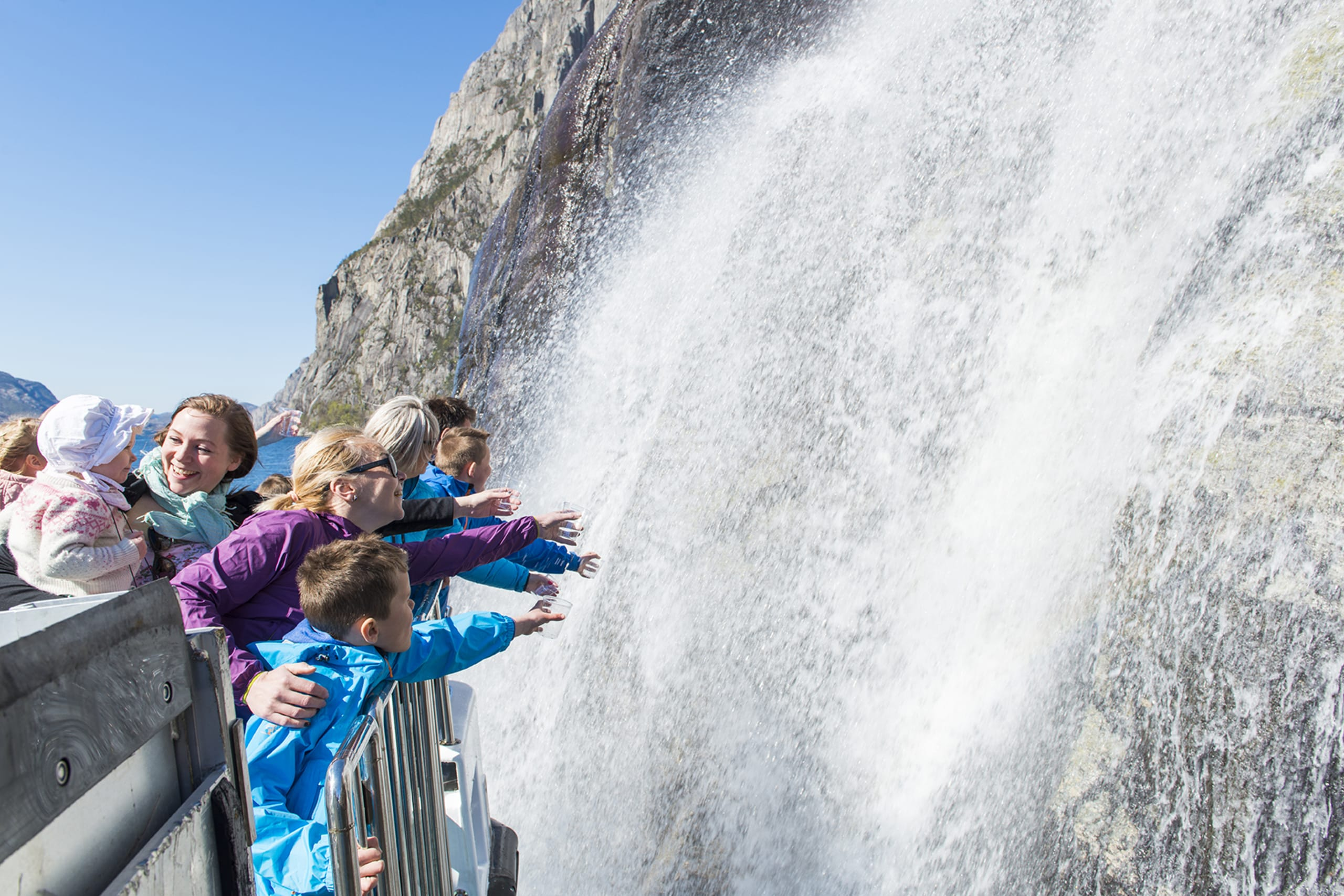 Tourists reaching for the fresh waterfall water from a cruise boat by Hengjane falls in the Lysefjord.