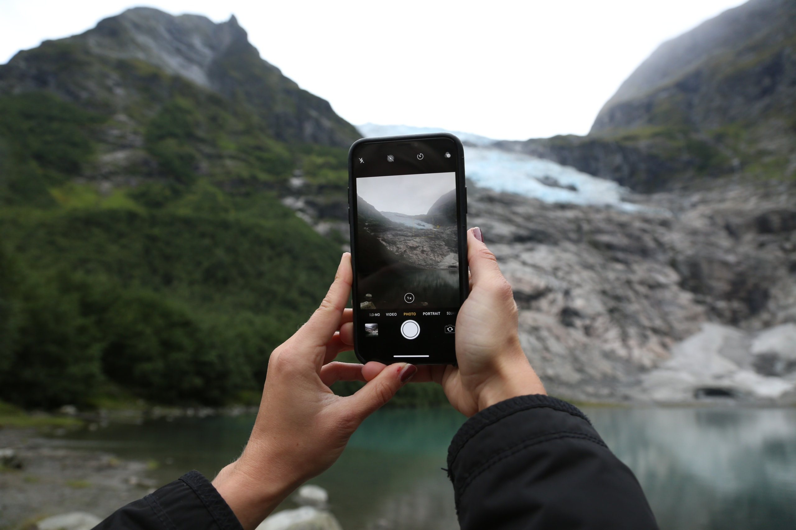 Woman taking a photo of the Bøyabreen glacier with an iPhone