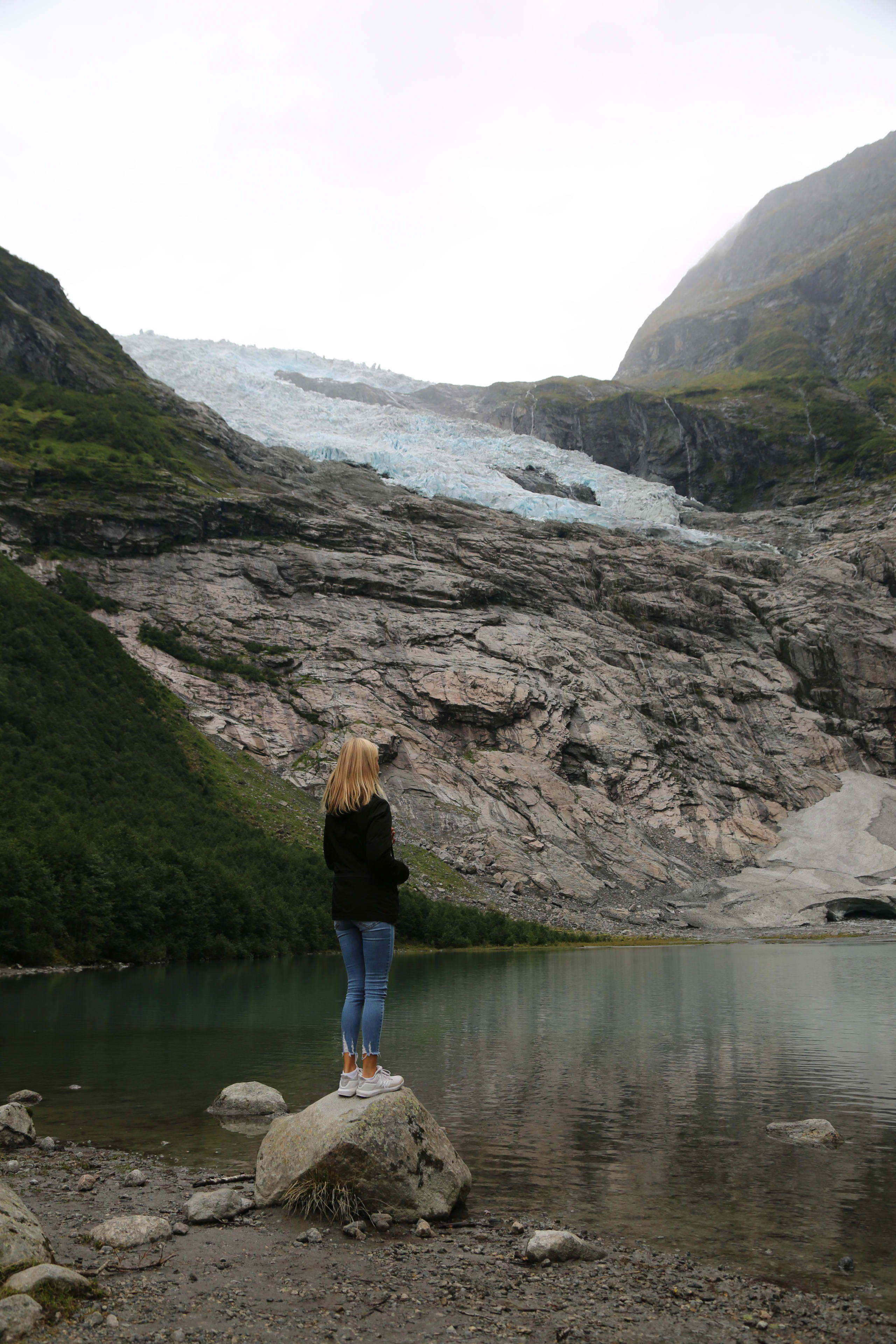 Woman standing on a rock close to the edge of a lake below Bøyabreen glacier