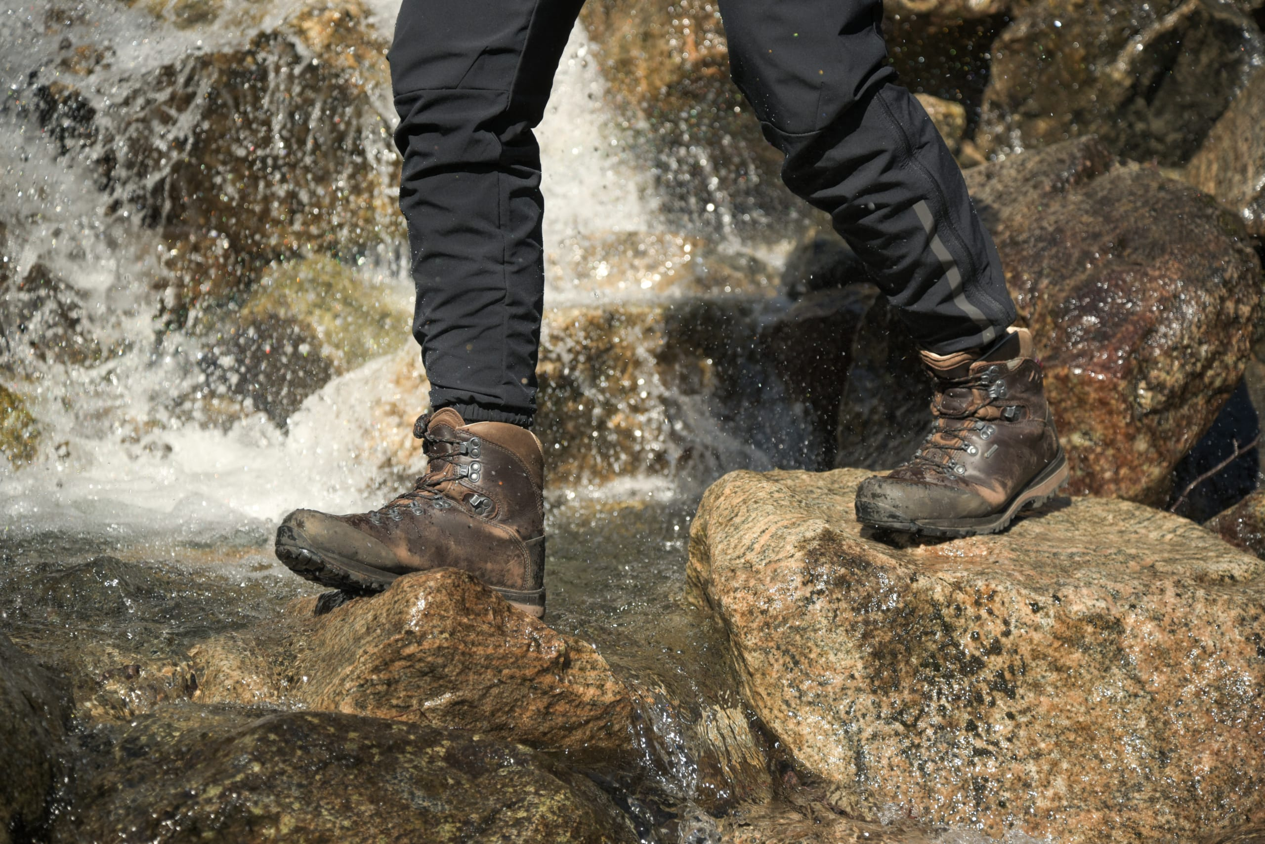 Person with proper mountain boots crossing a river