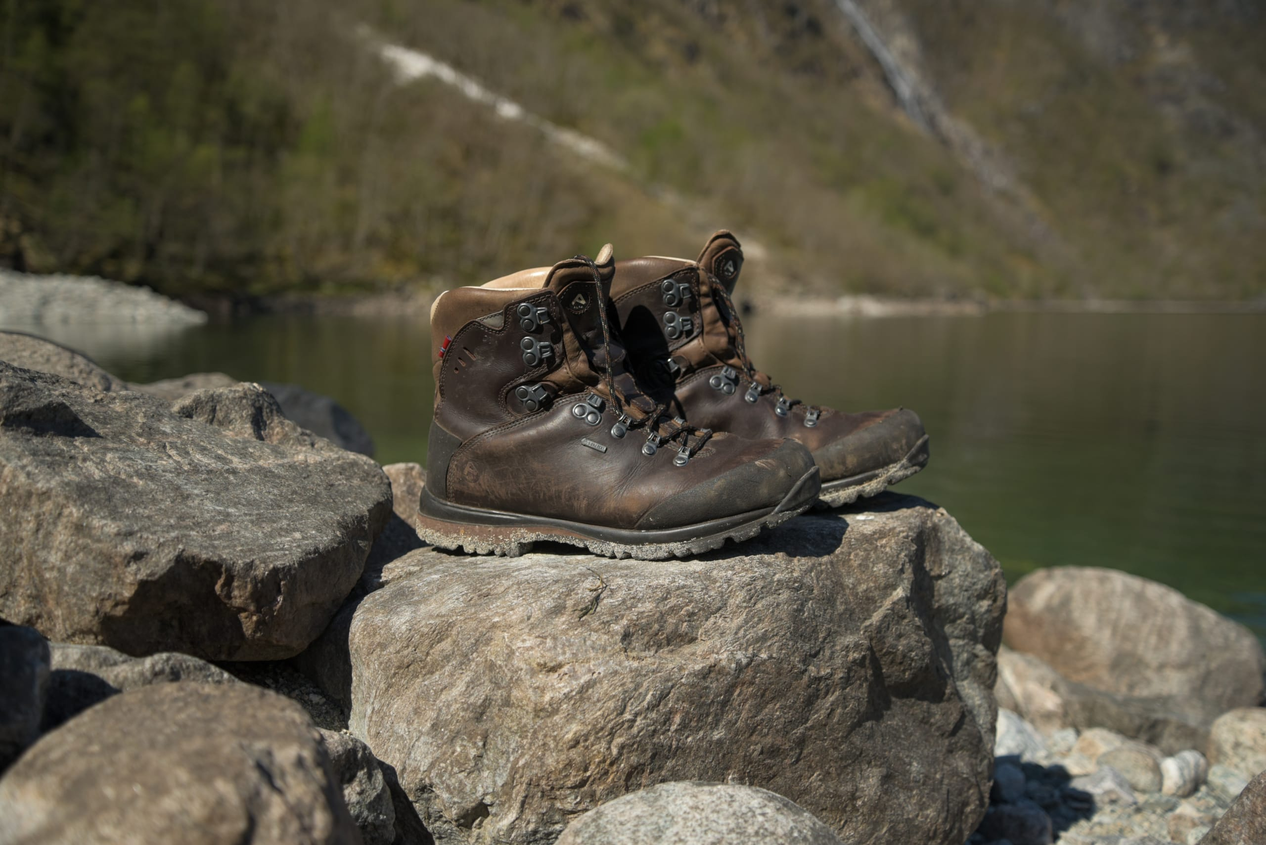 mountain boots on a rock close to a lake