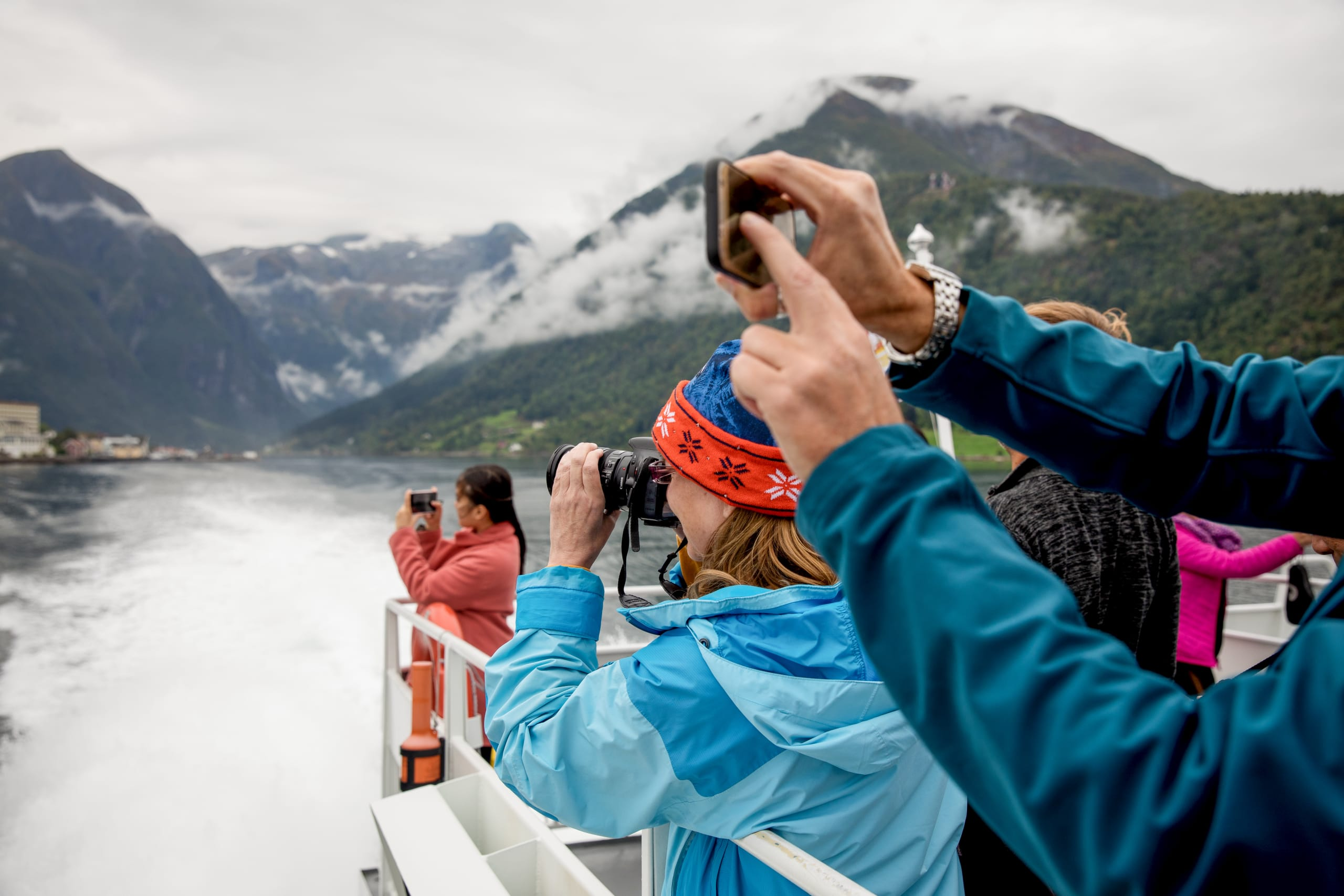 Tourists photographing at the sundeck of the fjord boat