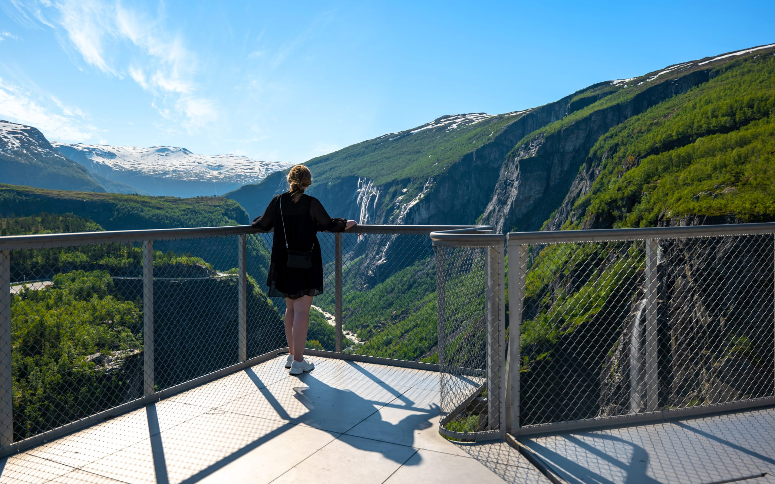 Woman standing on the view platform looking down at Vøringsfossen waterfall