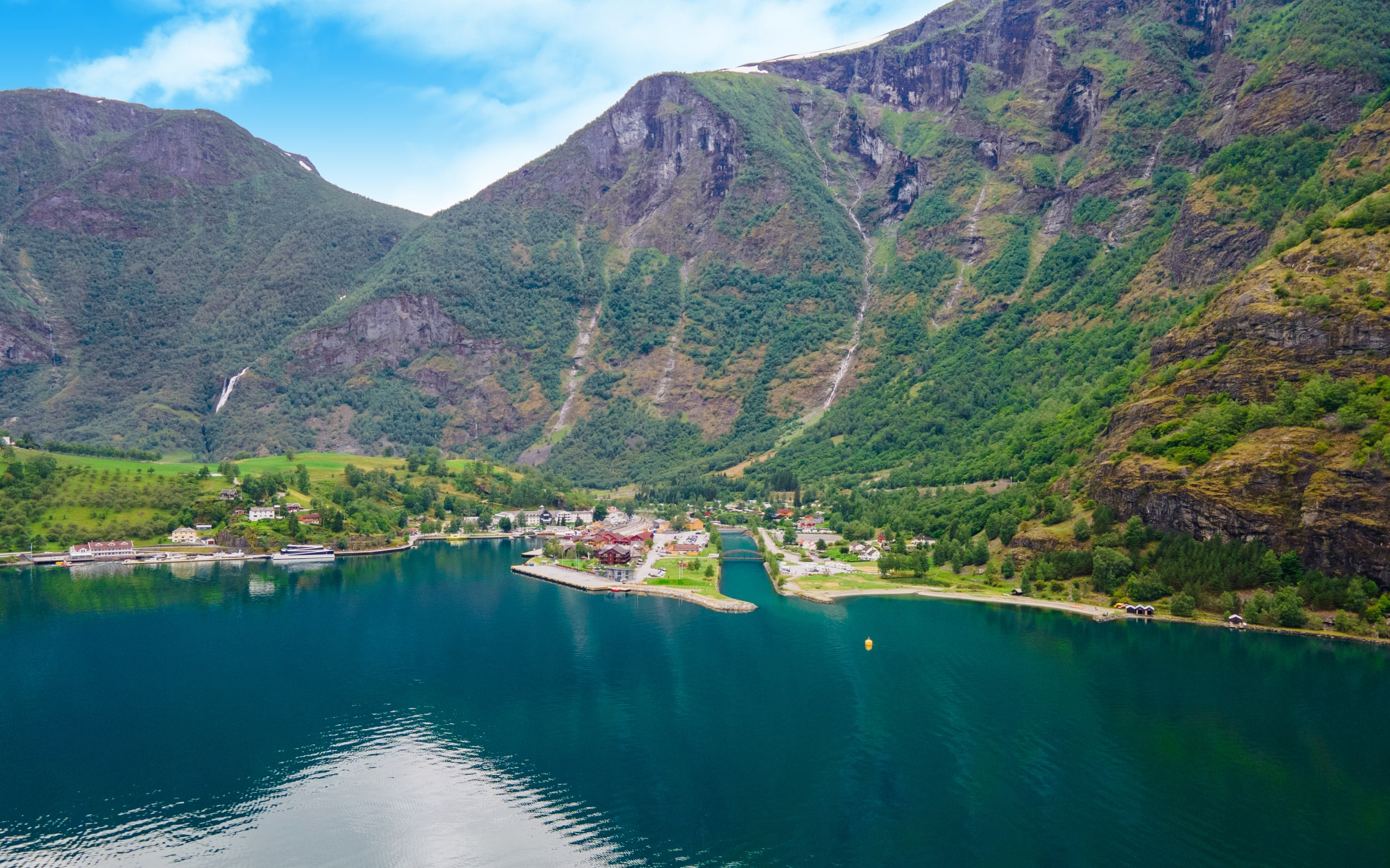 The harbor of Flåm with lush mountainsides