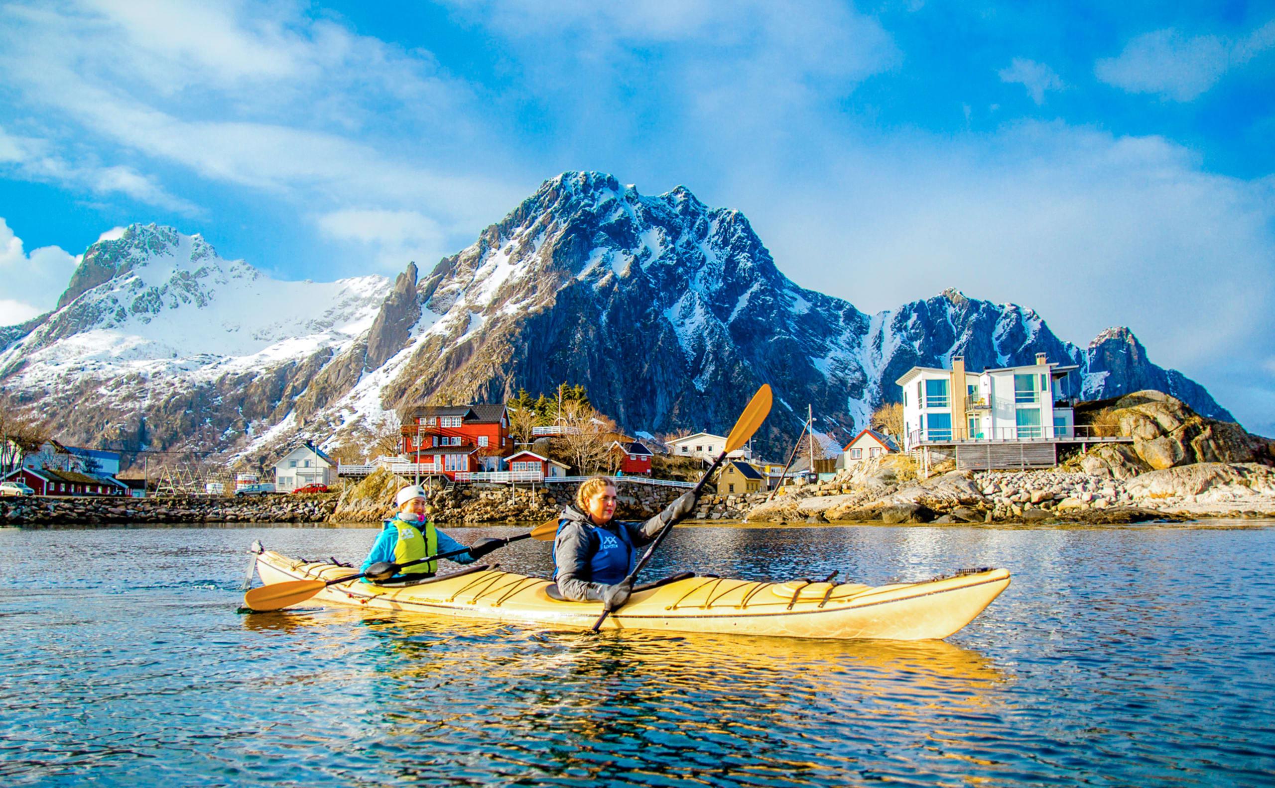 Girls in double sea kayak on safari in Lofoten