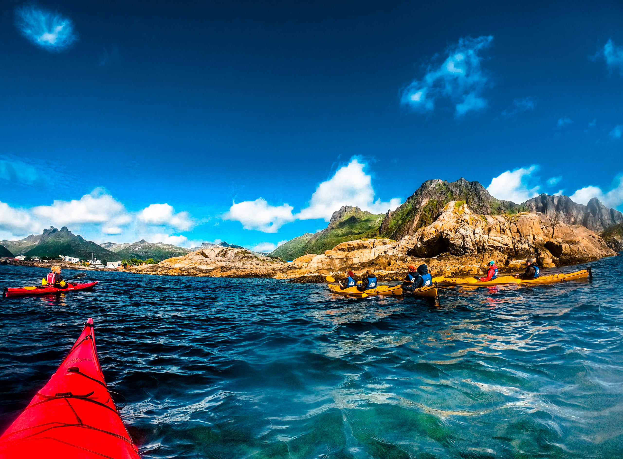 The tip of a red kayak facing 3 other kayaks in the crystal clear turquoise waters in Lofoten with steep mountains in the background.
