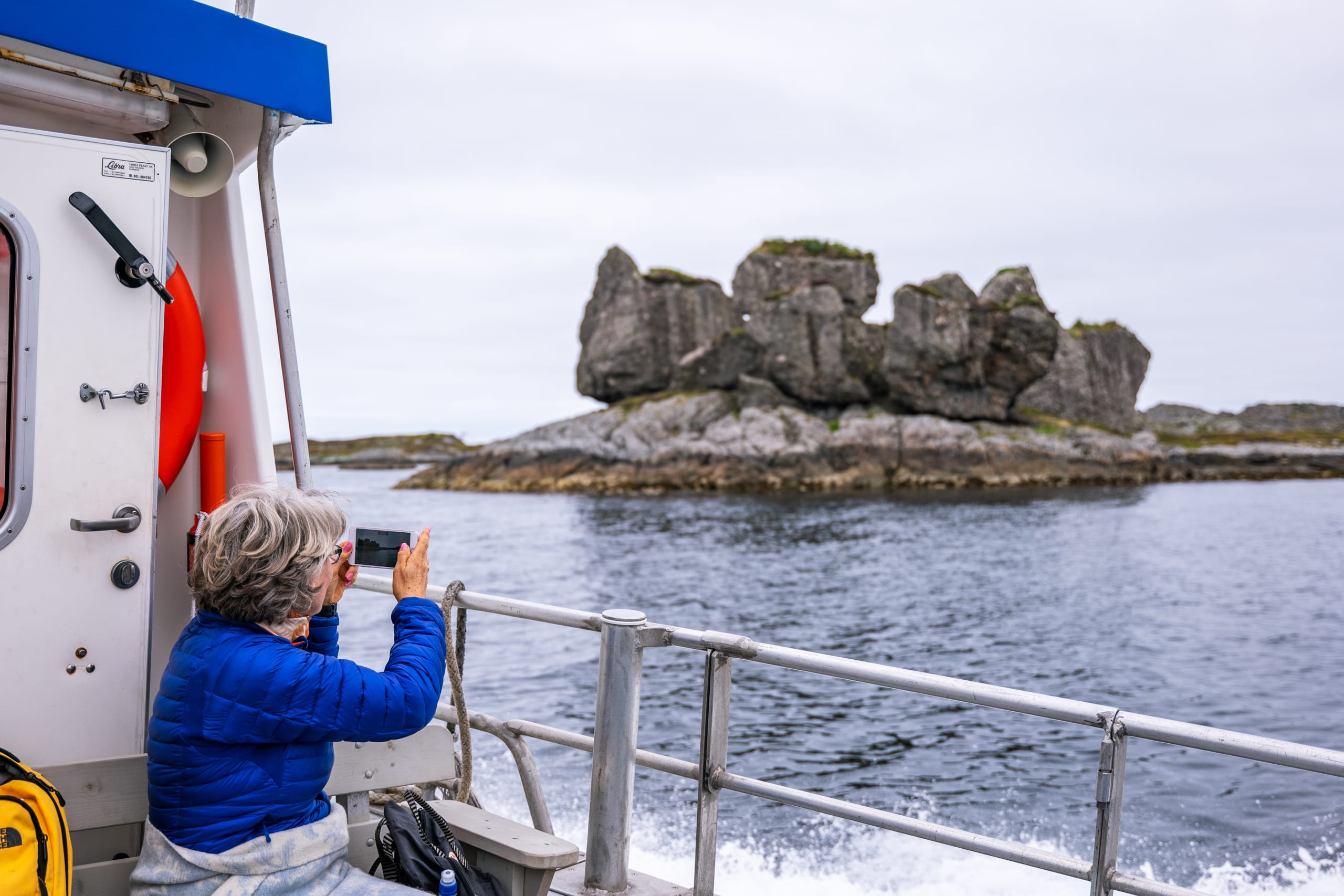 Woman photographing the Lågøystolane
