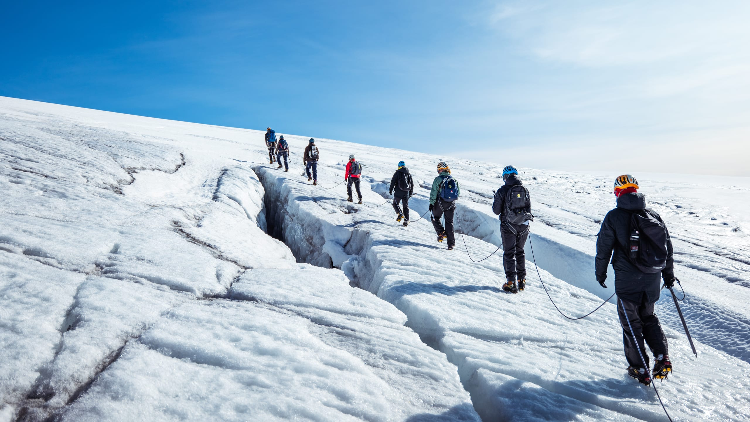Glacier hike between deep crevasses in the ice