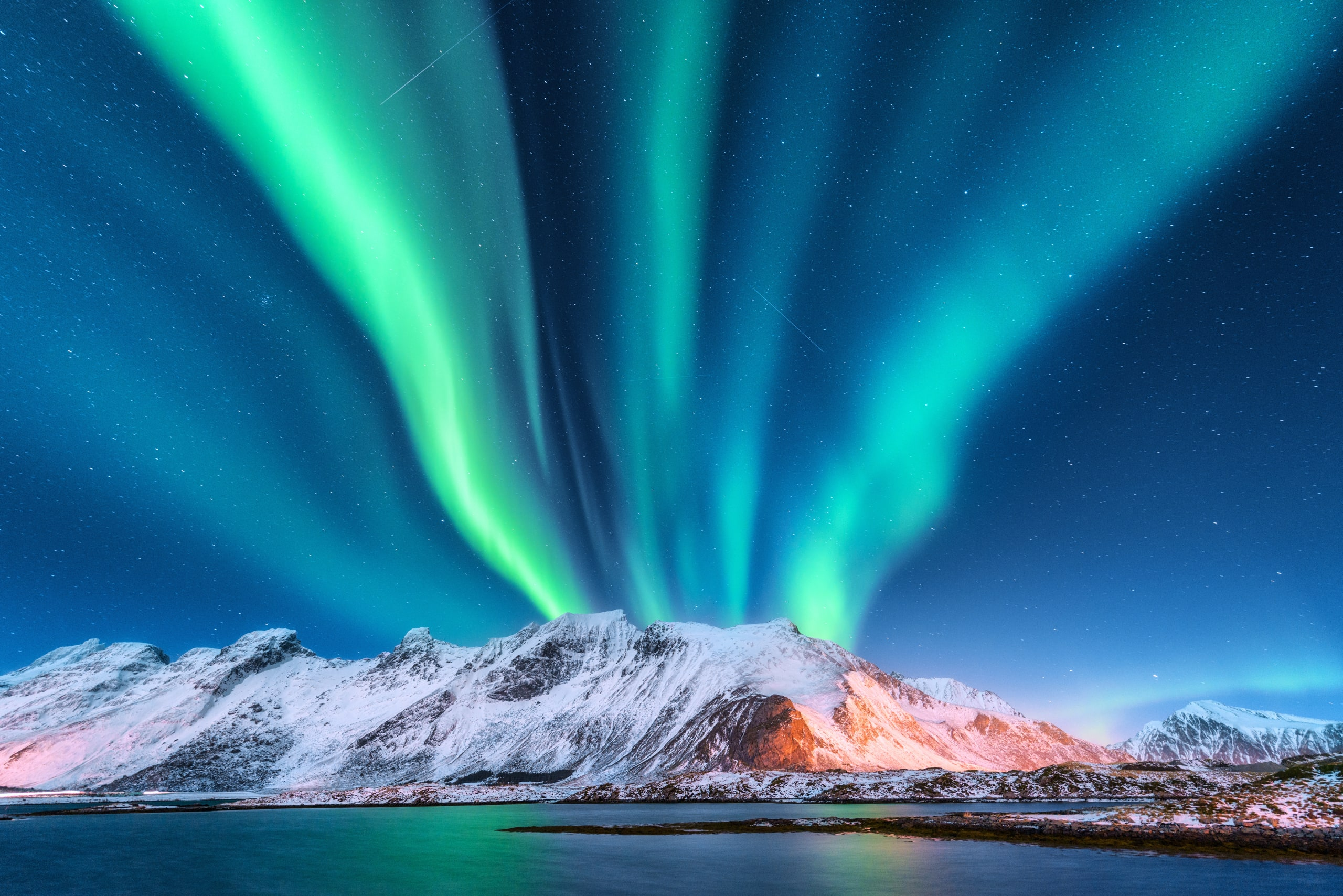 Dancing lights above snow capped mountains in Lofoten.