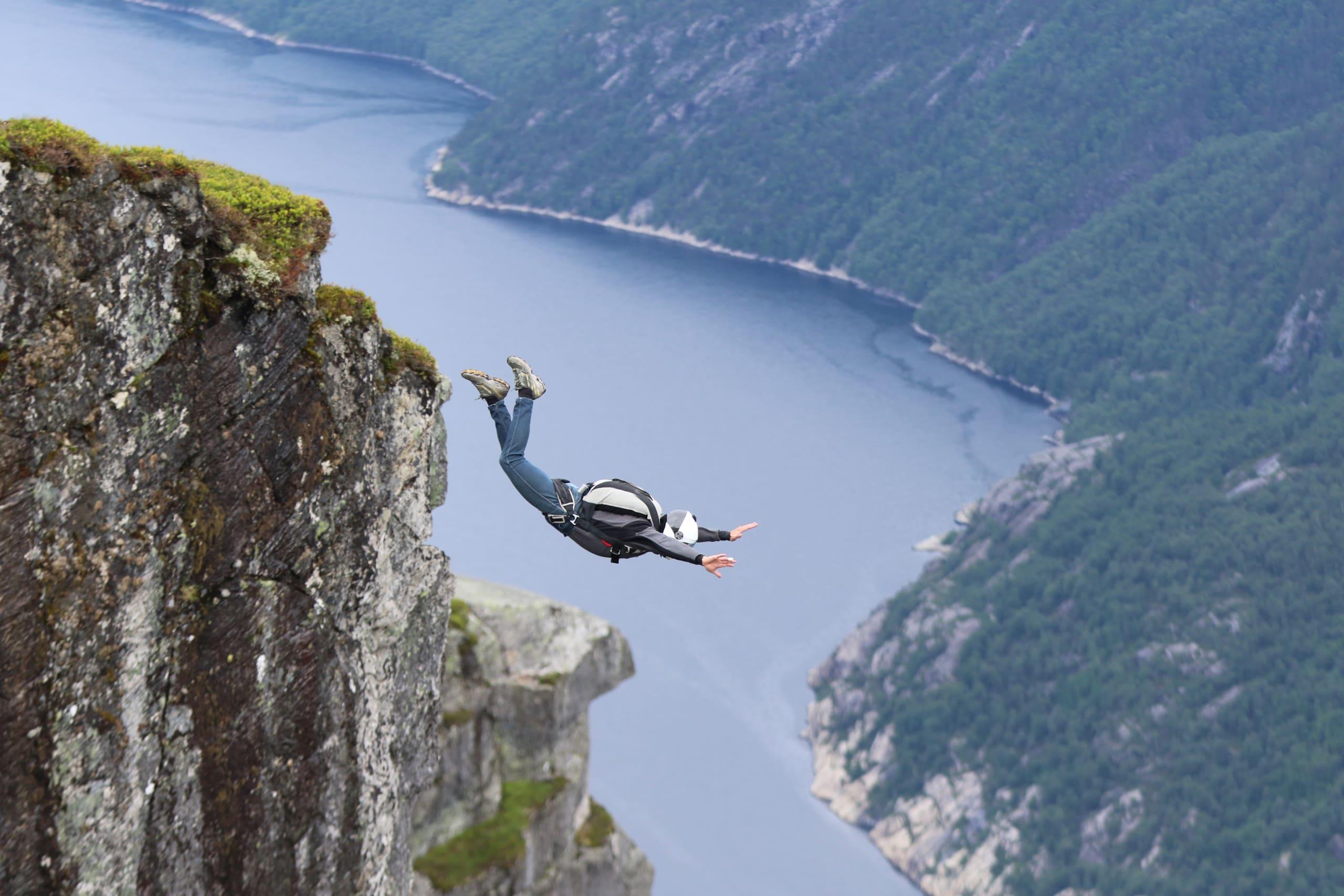 Base jumper flying off the cliffs of Kjerag