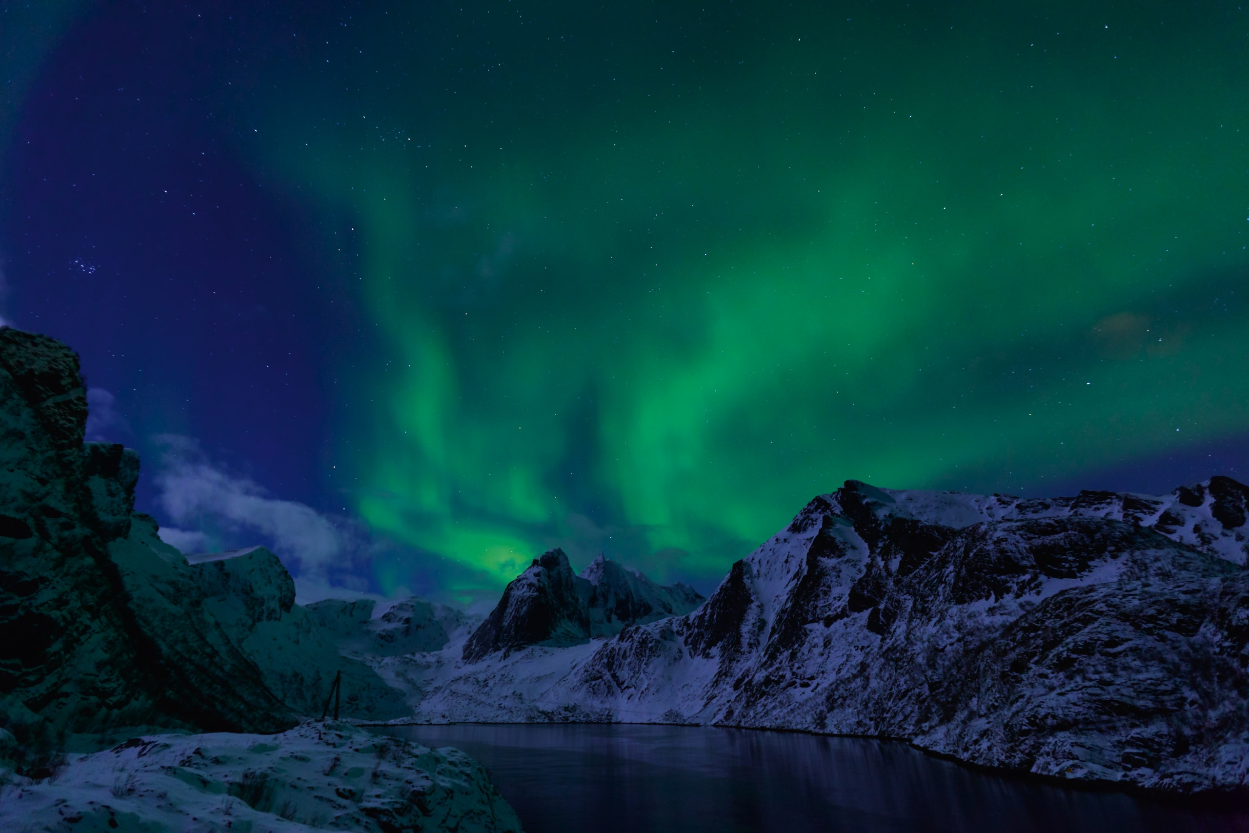 Northern lights over Lofoten's sharp mountains.