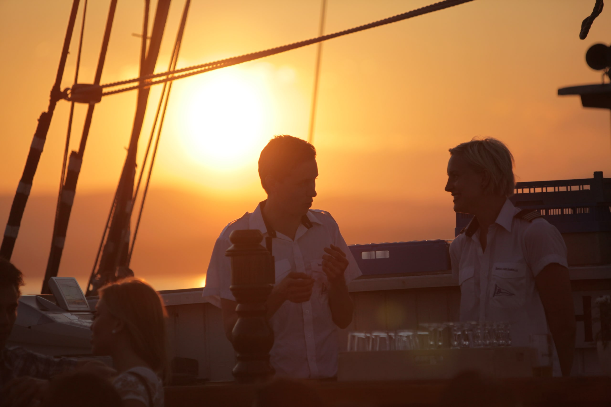 Crew on the sailship in sunset