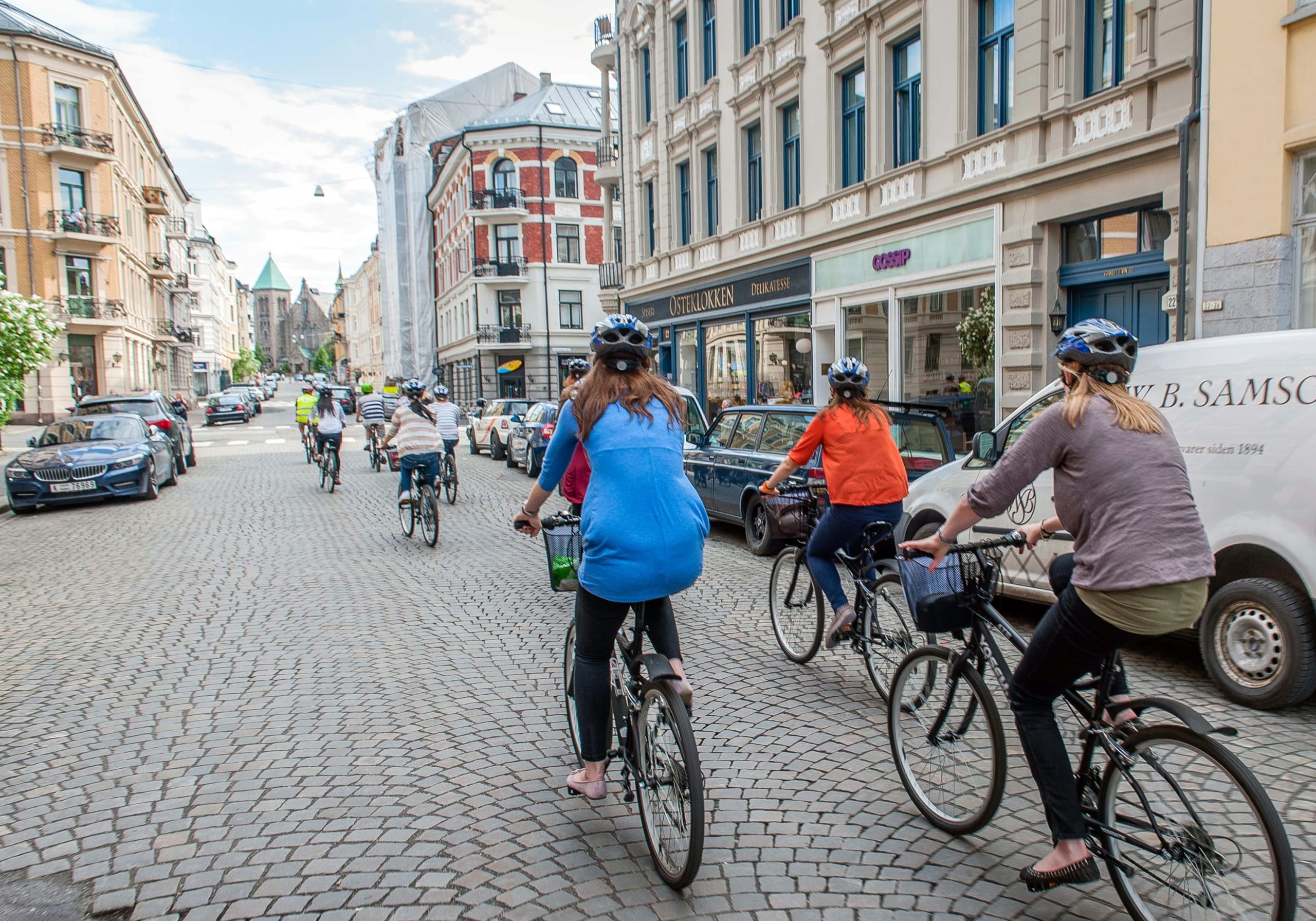 A group of bikers riding through cobble stone streets downtown Oslo.