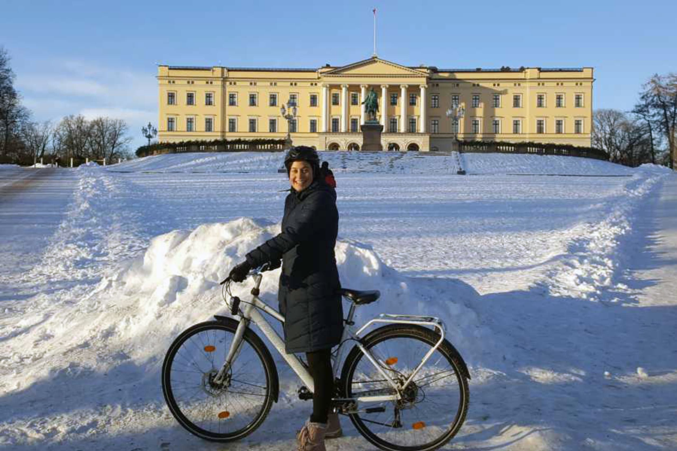 A woman smiling at the camera while biking in the snow in downtown Oslo. The King's Palace is featured in the background.