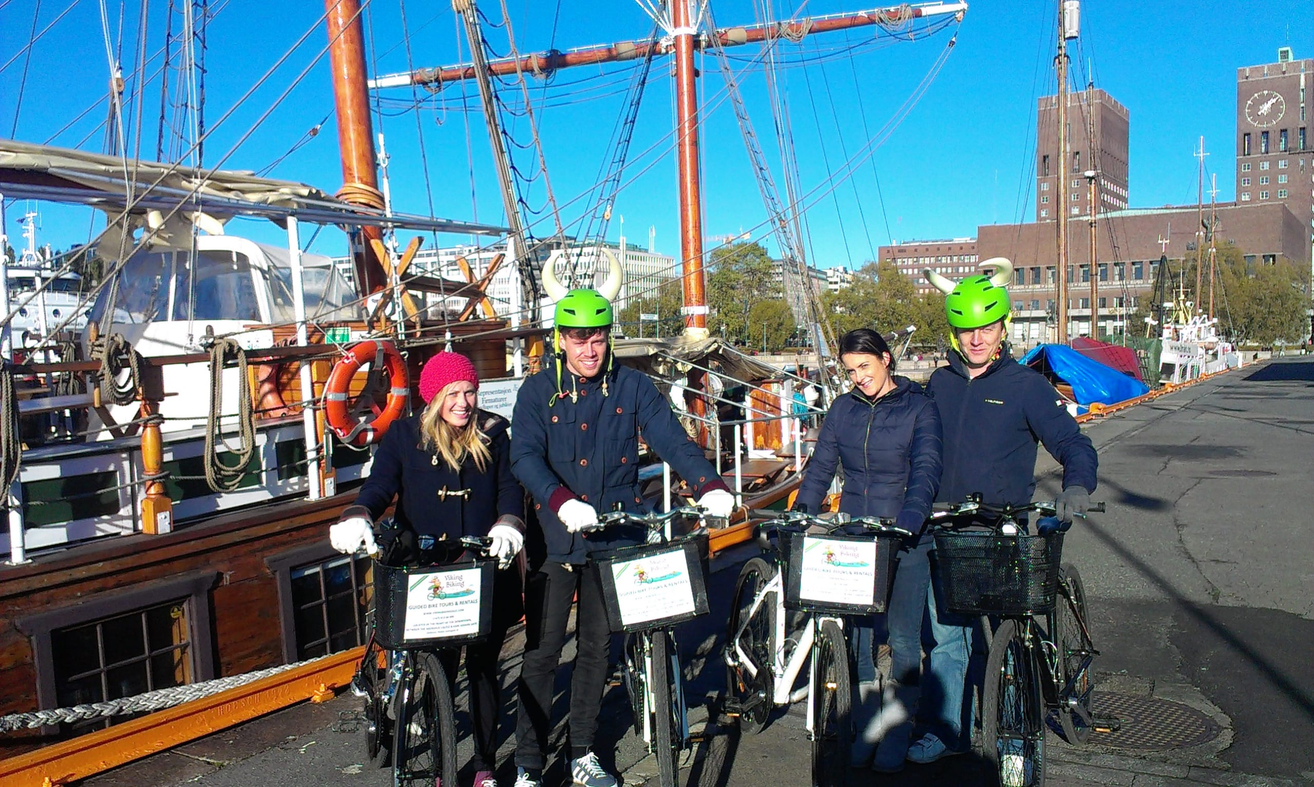 4 smiling tourists standing next to their bikes in the Oslo harbor with a big wooden sail boat featured in the background.