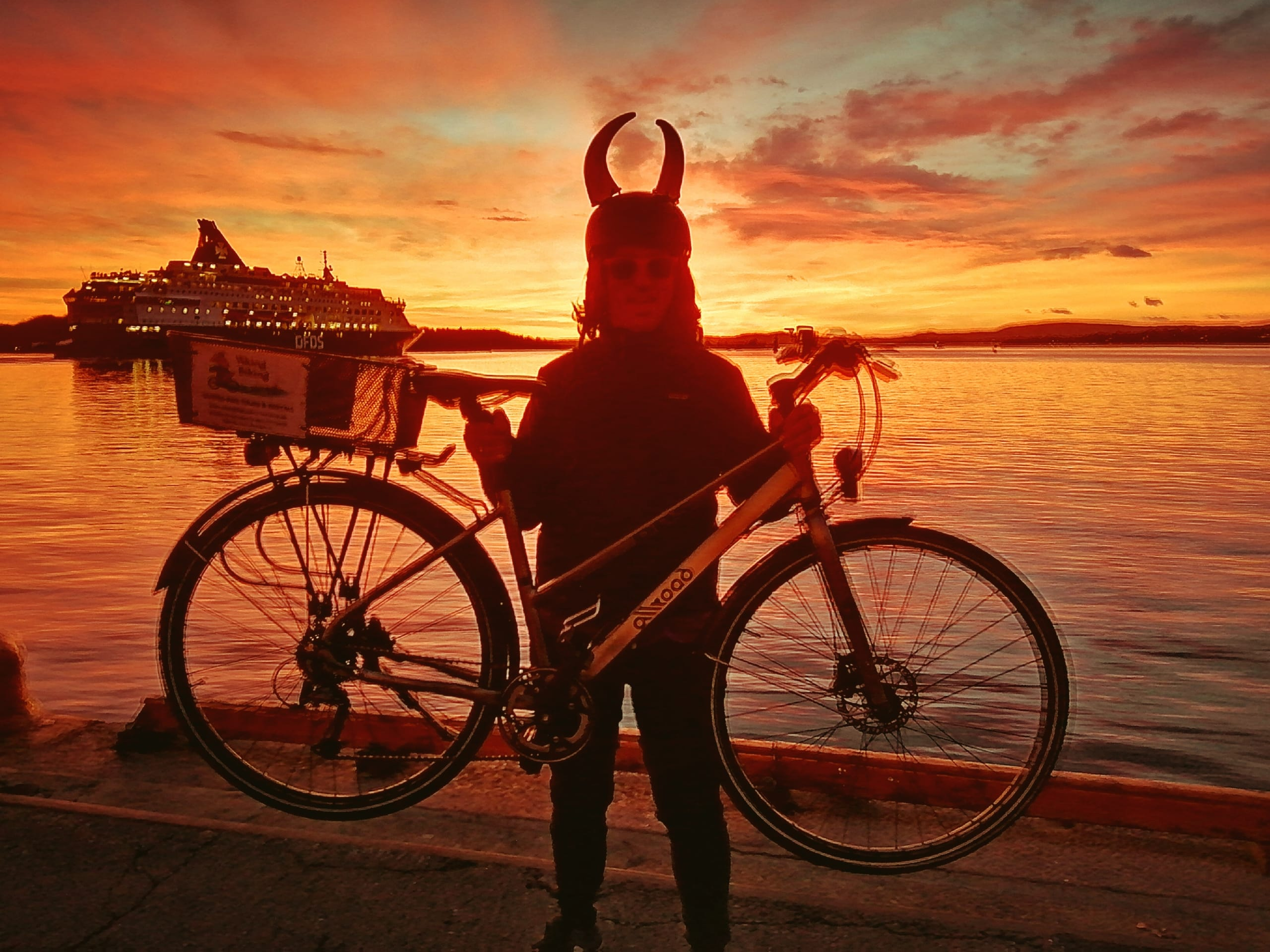 A man wearing a viking helmet while lifting his bike. A vivid red sunset is playing out in the background.