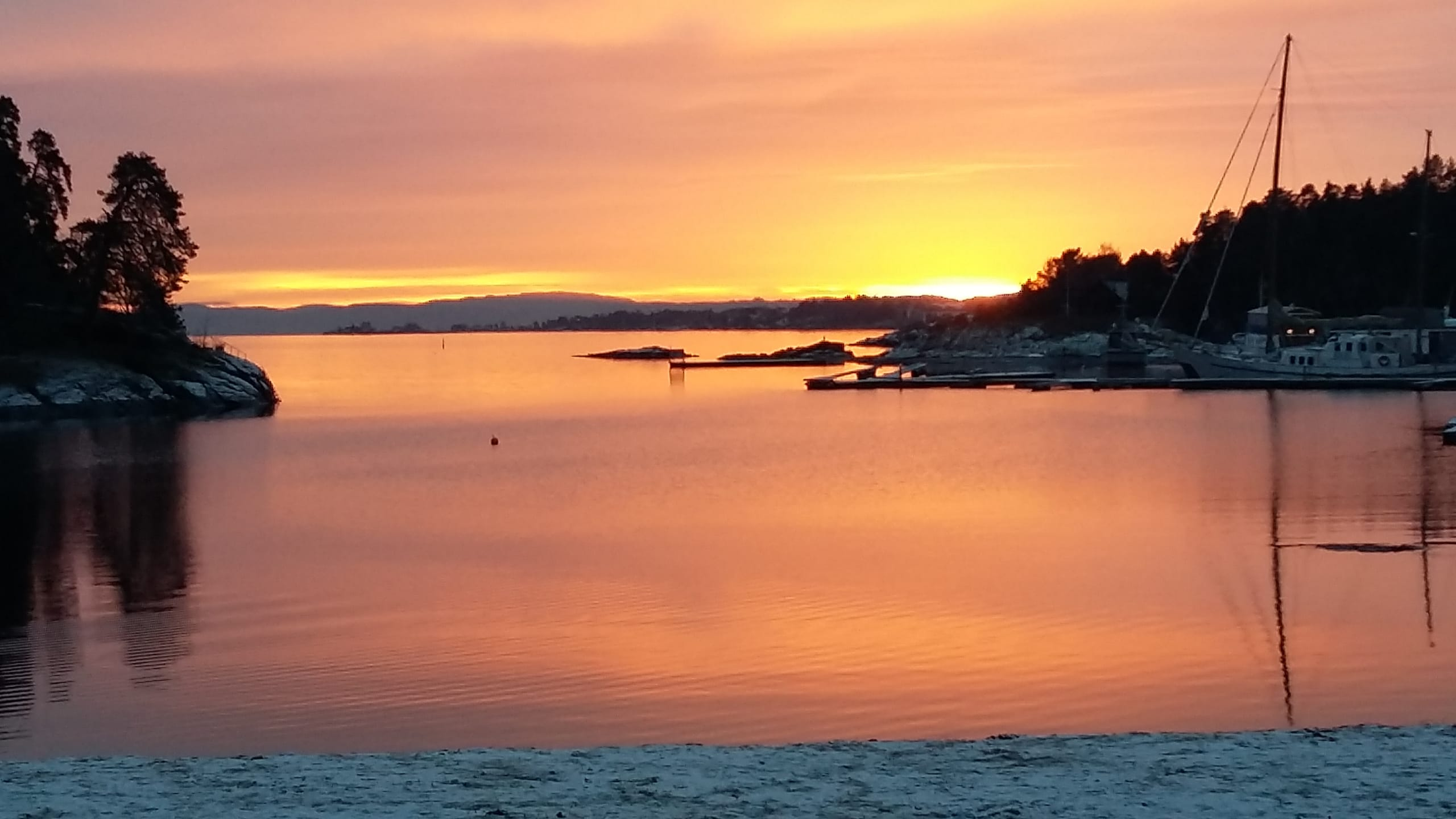 A coastal view featuring a bright red sunset in Oslo.