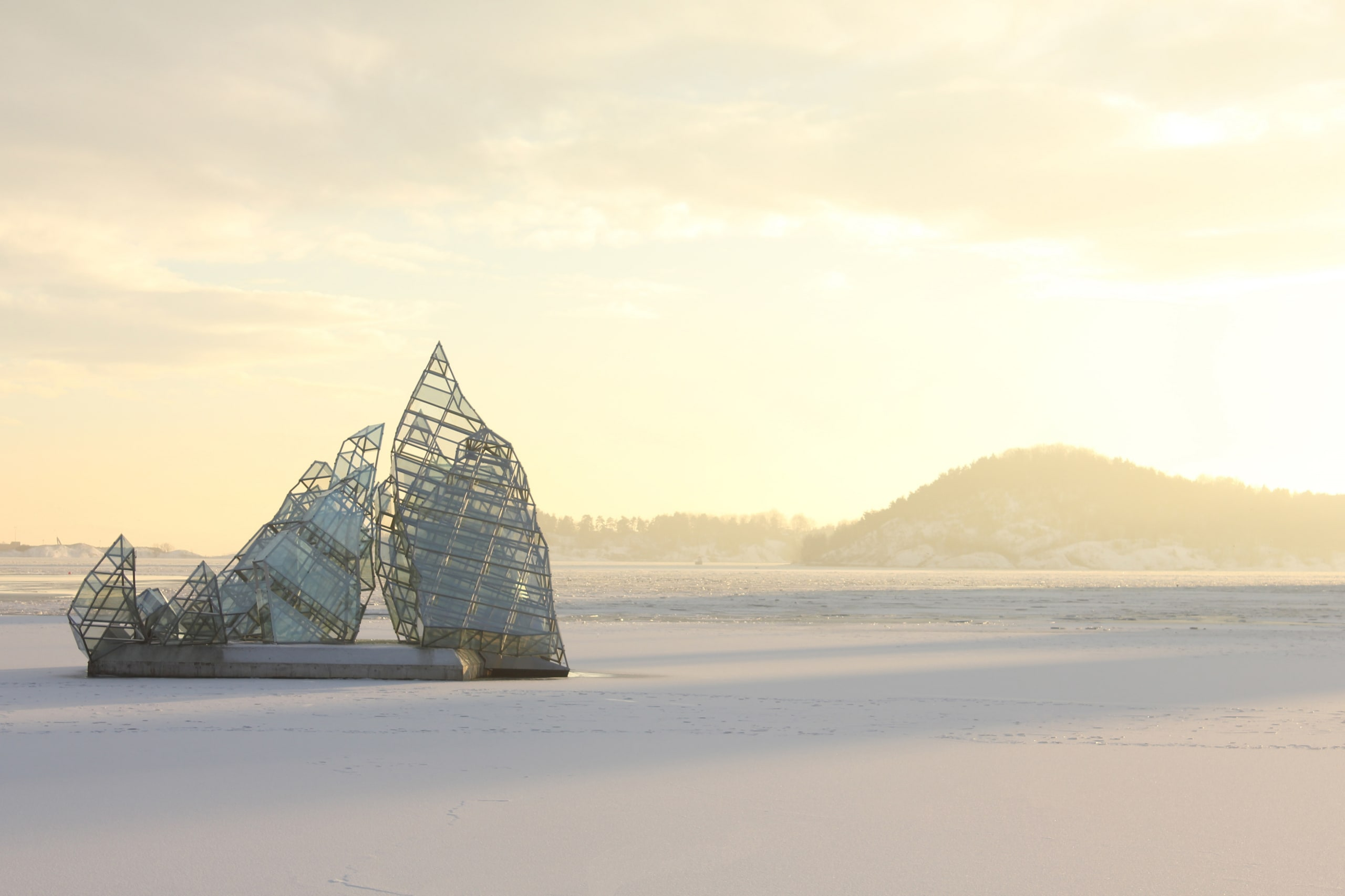 A sculpture on frozen water featured in golden winter light in downtown Oslo.