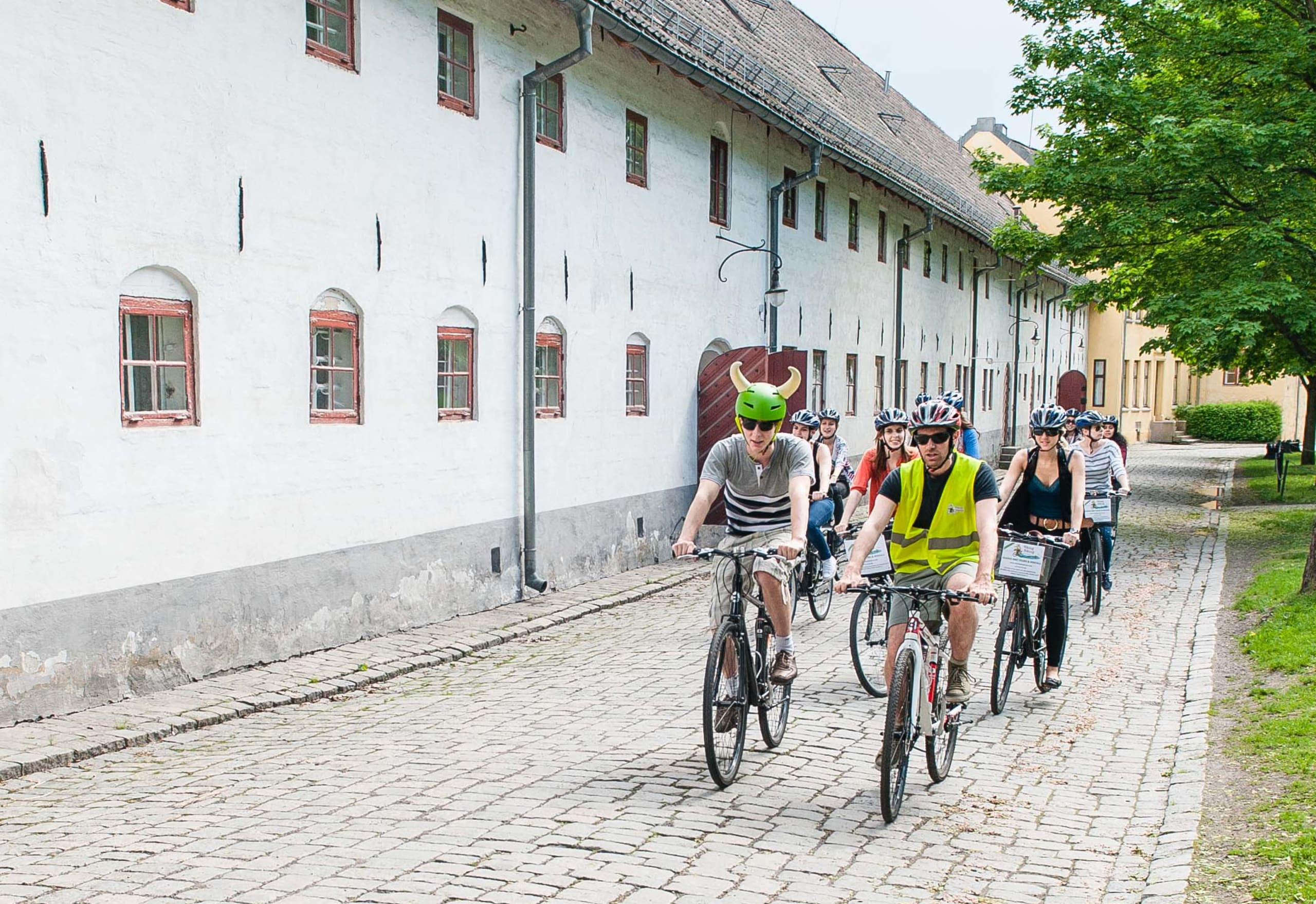 A group of tourists exploring historical sites in Oslo by bike.