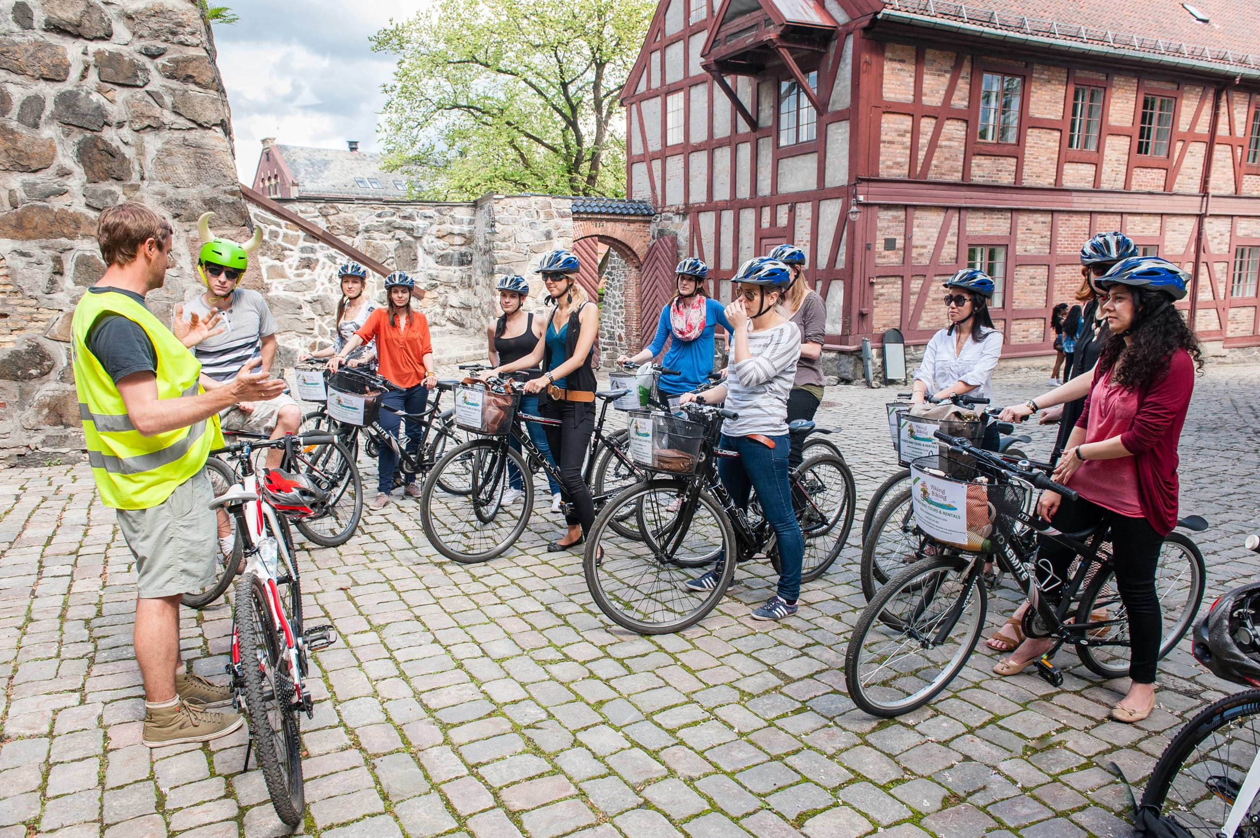 A group of tourists are being guided around historical parts of Oslo by bikes.