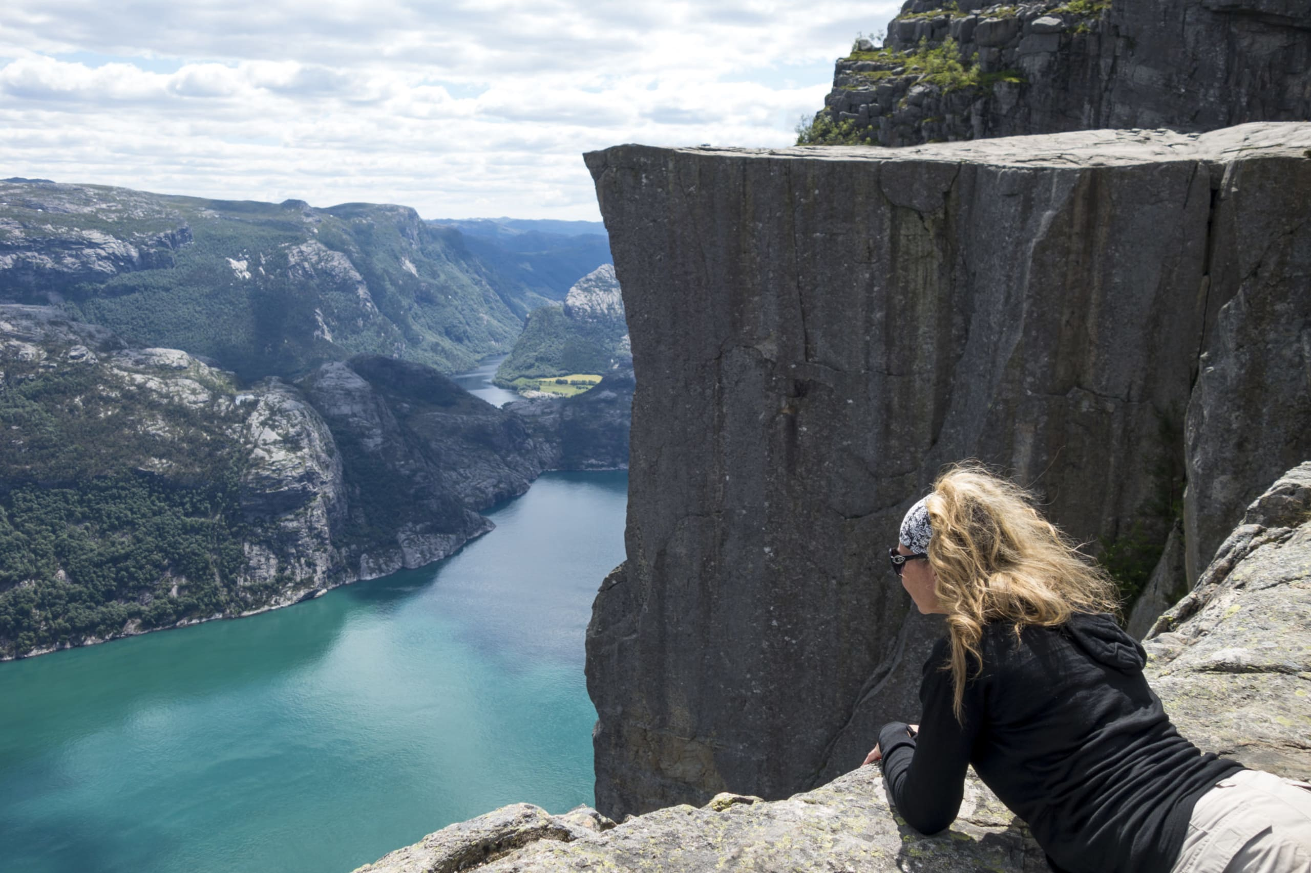 Woman leaning over the edge of Preikestolen