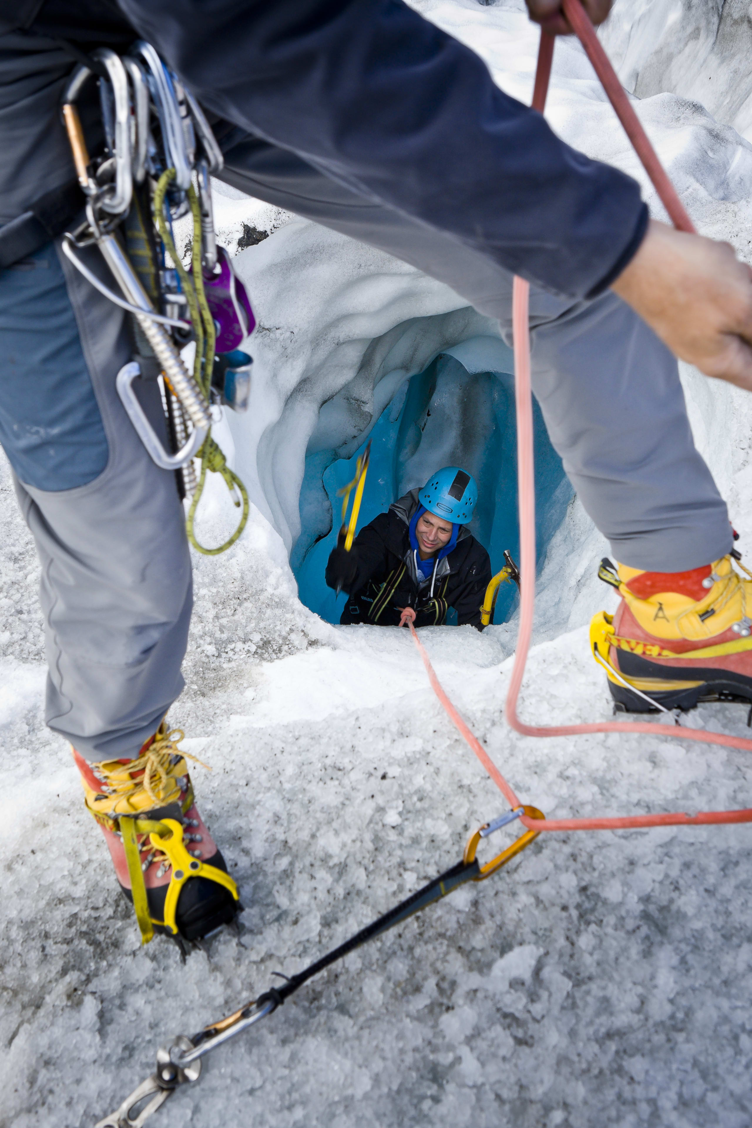 Glacier hiking through an ice tunnel