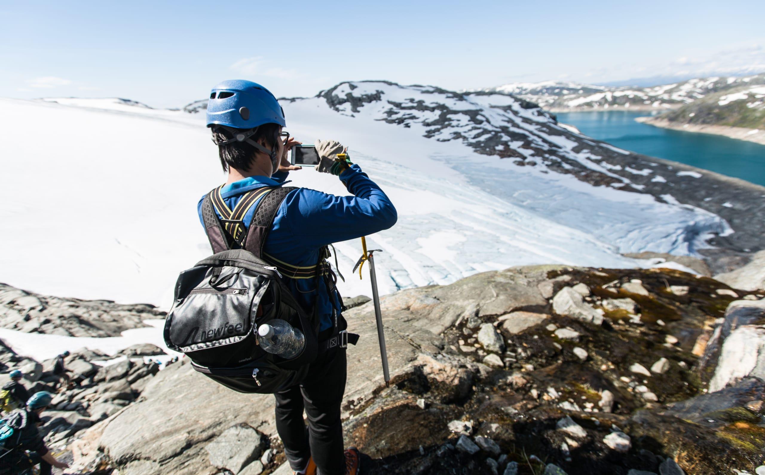 Glacier hiking taking photo at viewpoint overlooking Folgefonna