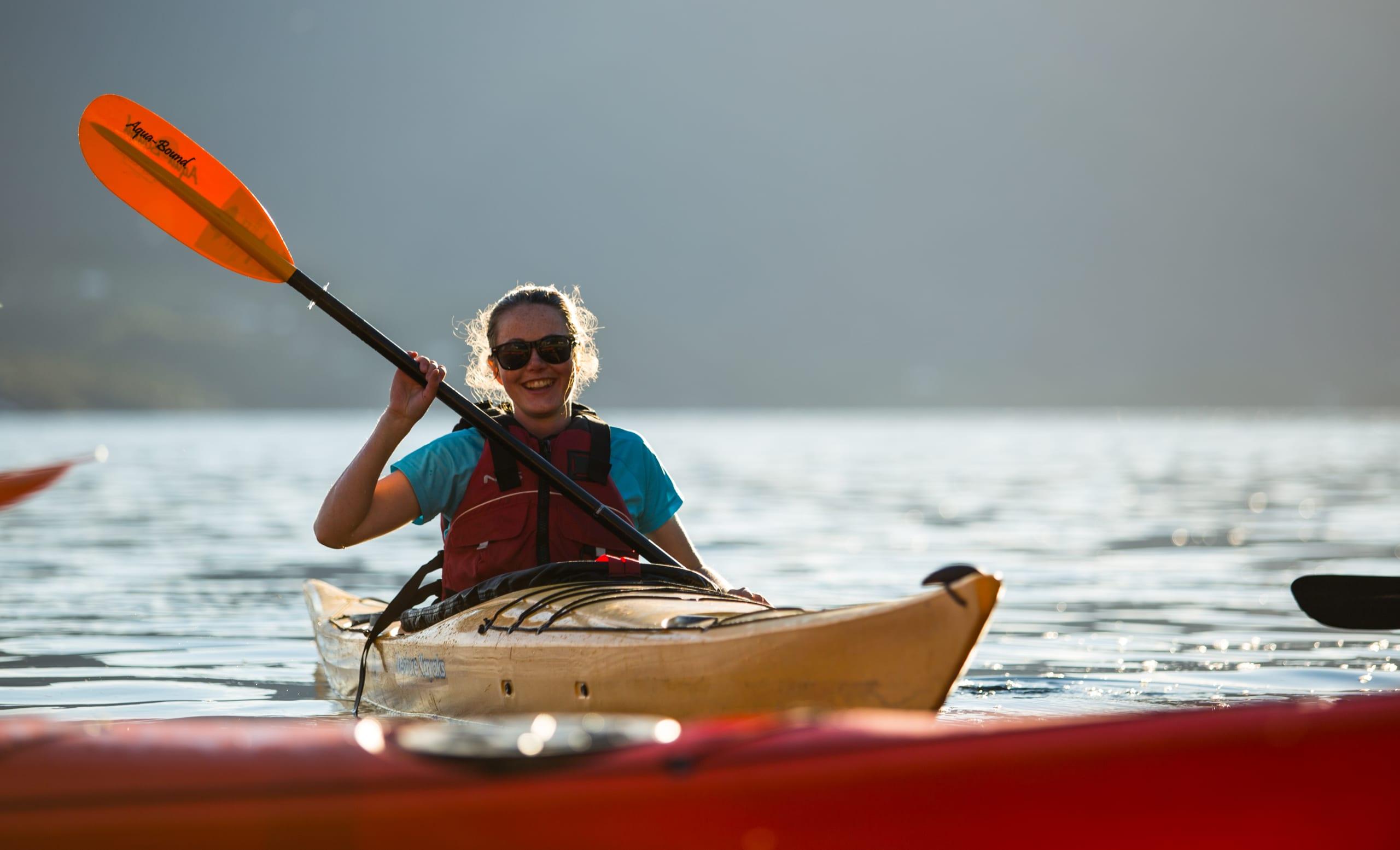 Smiling girl kayaking on the Hardangerfjord