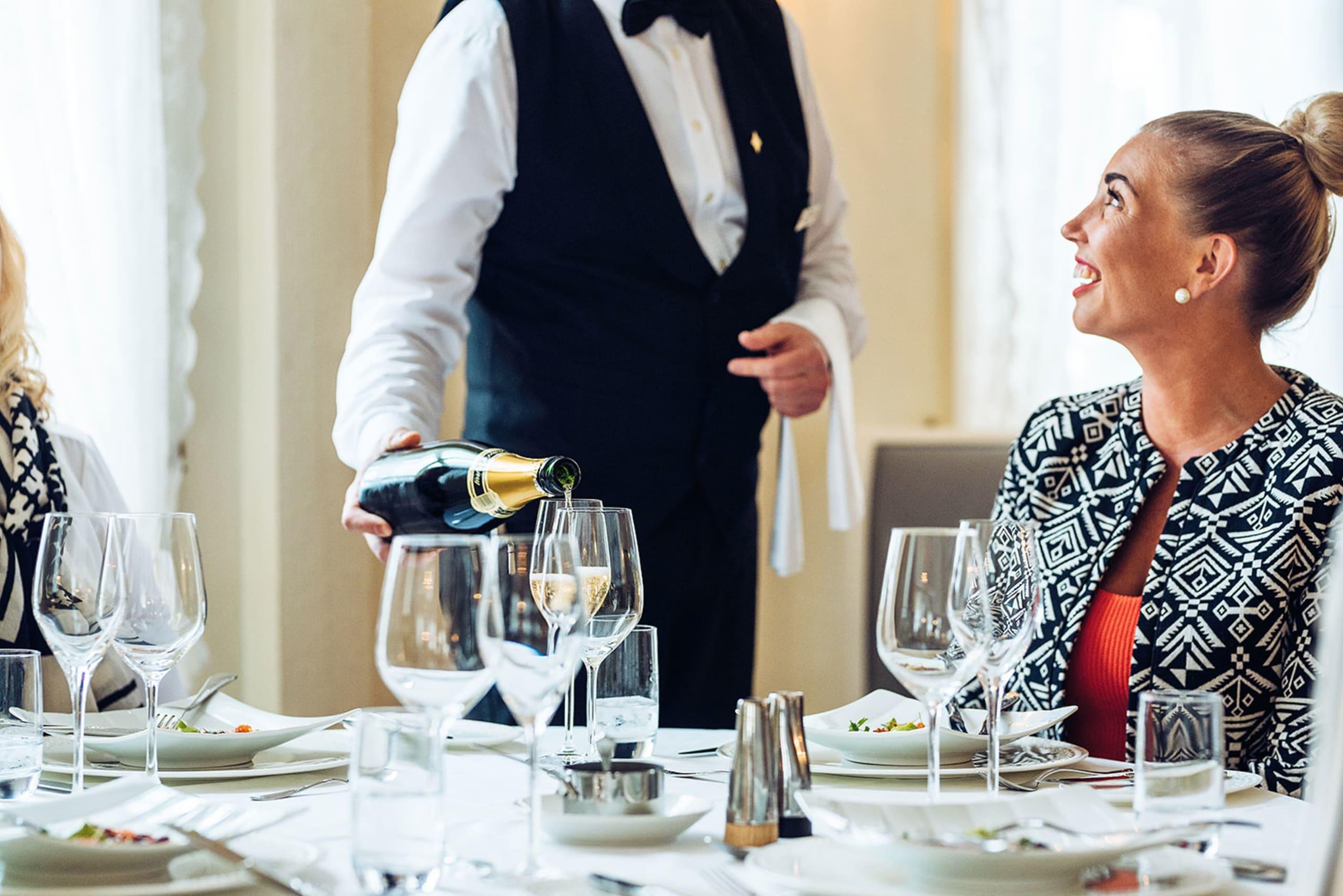 Lady who is served champagne at Bekkjarvik Gjestgiveri