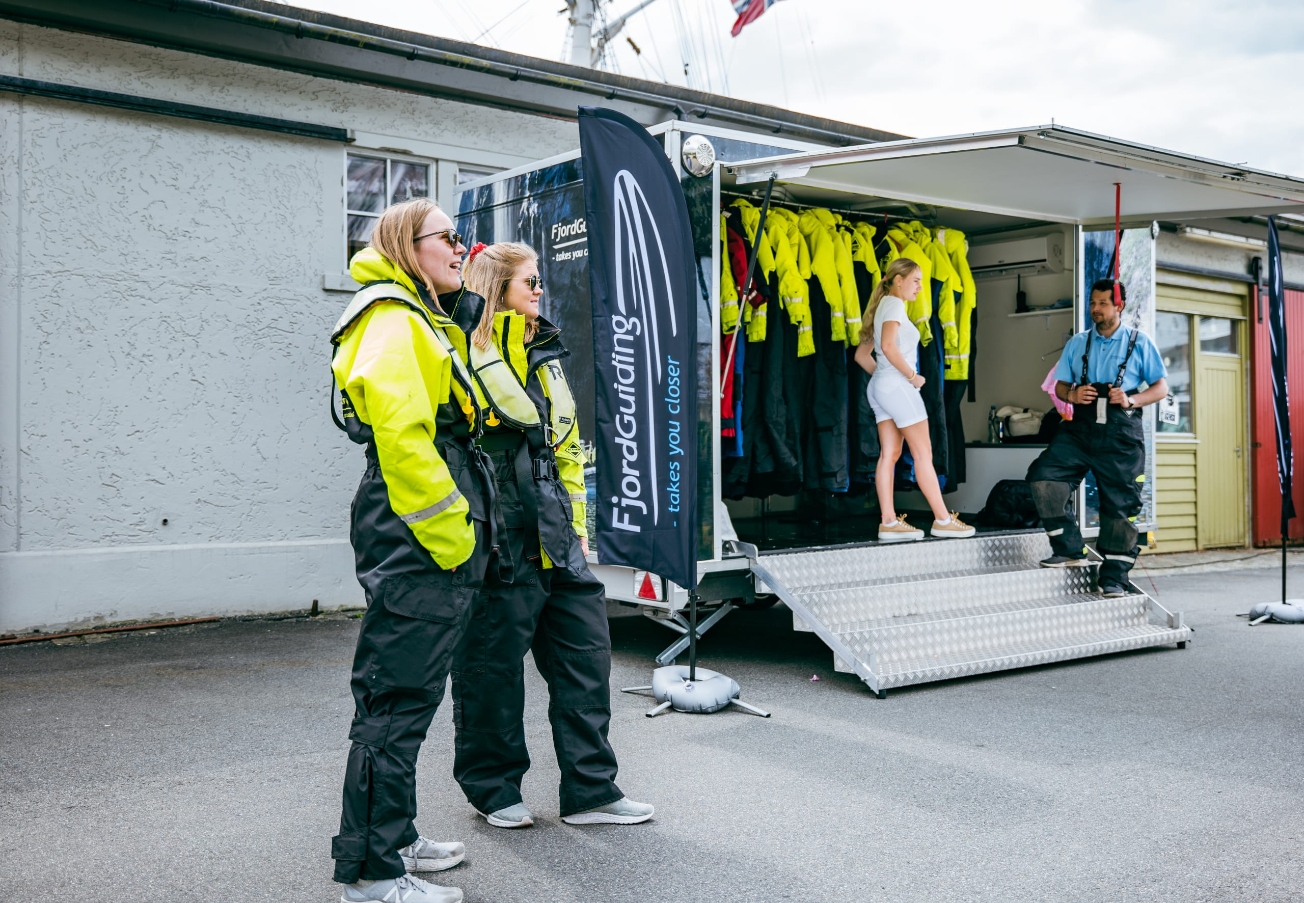 Girls dressed in safety suits next to Bergen RIB trailer