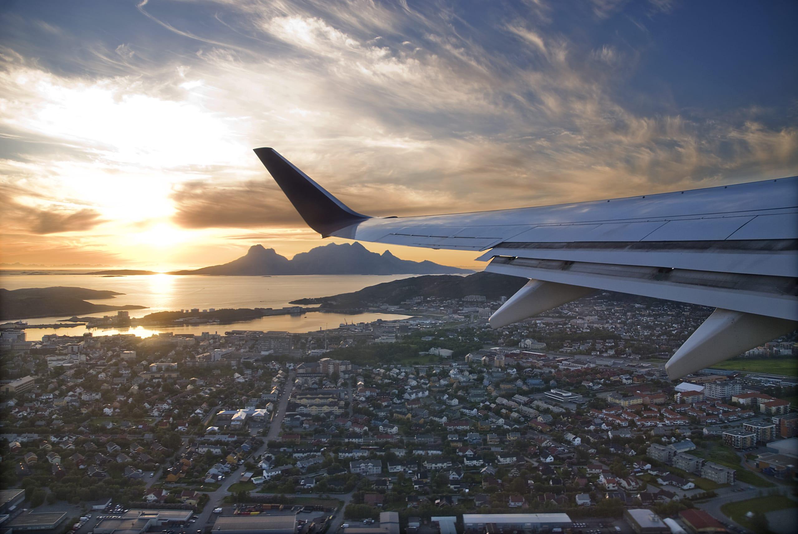 Plane flying over Bodø city at sunset