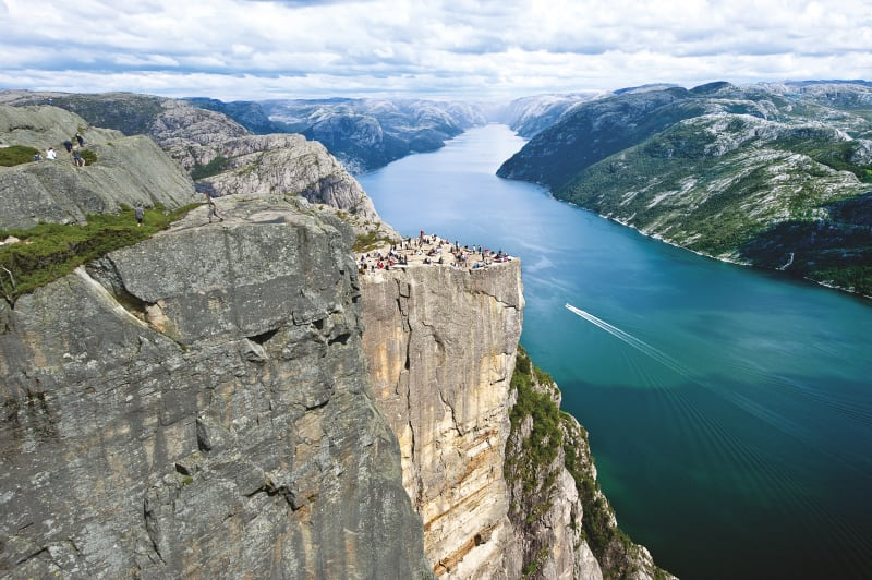 Preikestolen seen from a bird's perspective from the side leaving the Lysefjord as a backdrop for the square plateau that is dotted with hikers.