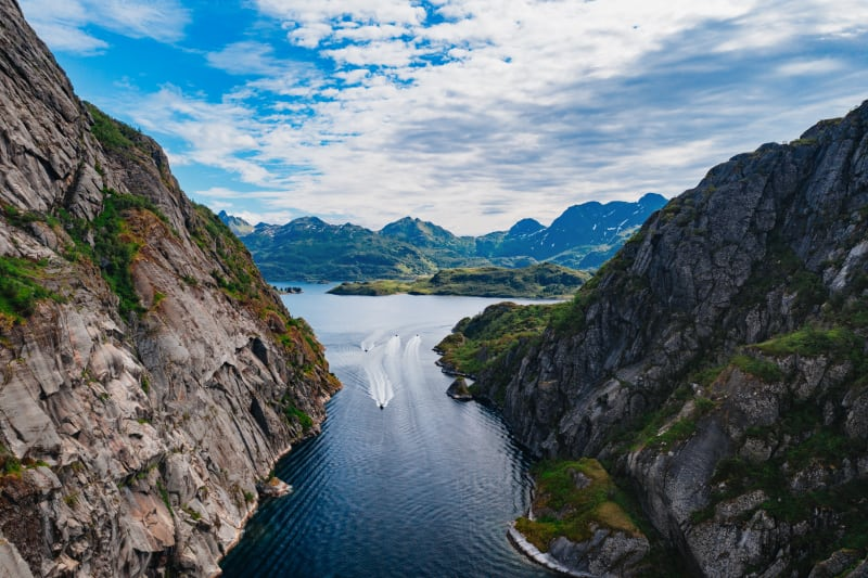 A bird's view of boats heading in and out of the narrow Trollfjord in Lofoten surrounded by majestic rock mountain sides.