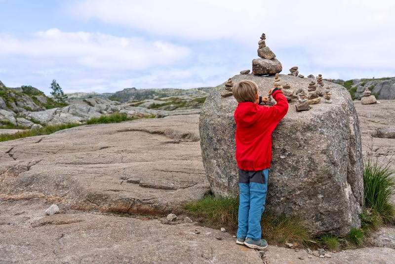 A kid playing on the hike to Preikestolen