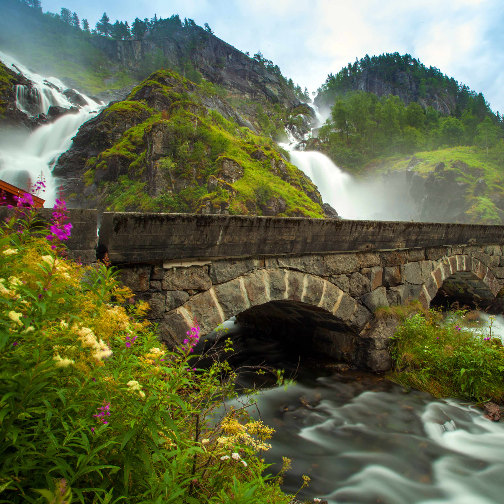 The powerfull Låtefoss is running down the mountainside in the summer time with a historic stone bridge with two arches is located by the foot of it.