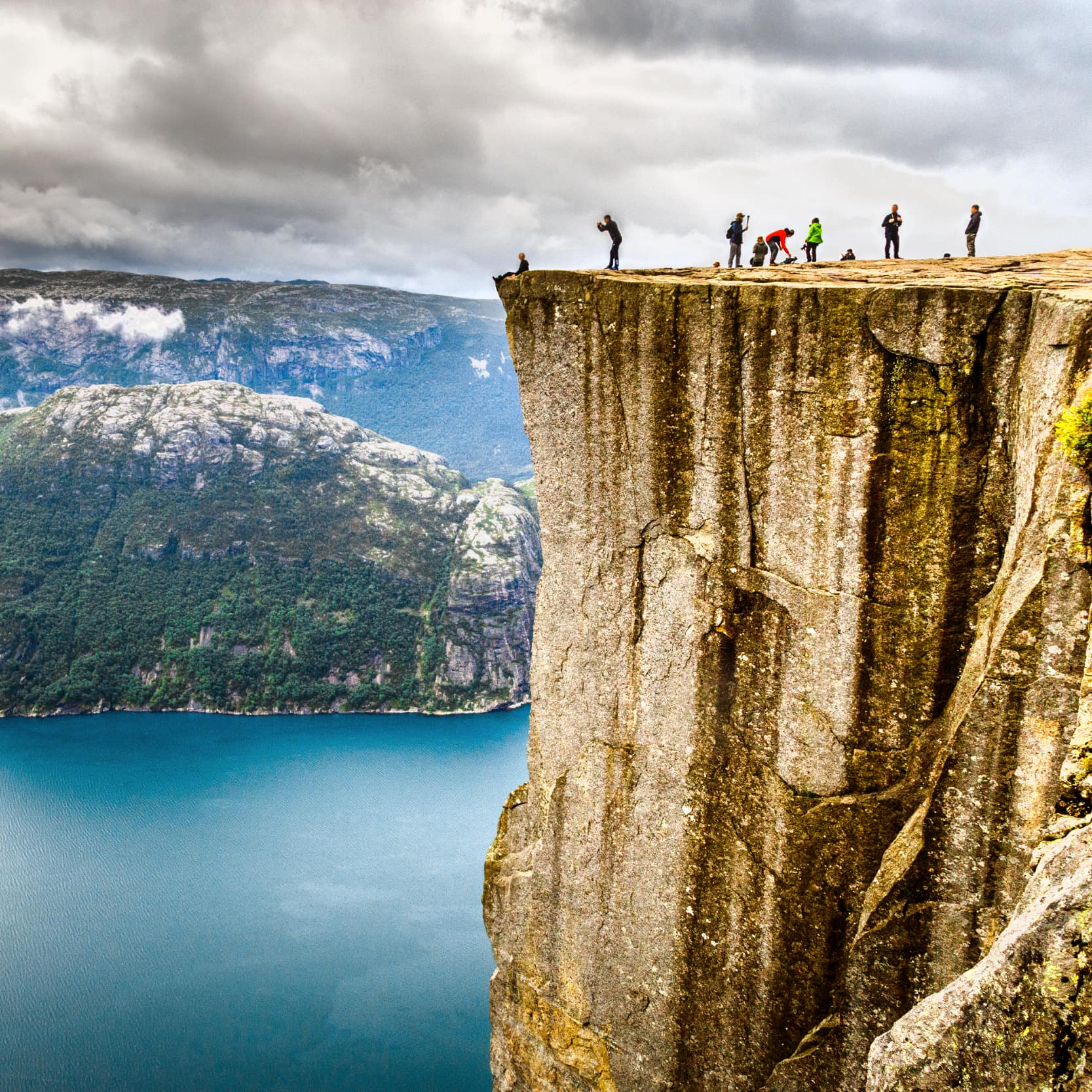 People walking upon Preikestolen, famous nature landmark in Norwey. Lysefjorden and mountains in background.